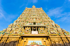 Madurai Meenakshi Amman Temple West Tower Centered. Centered west tower gateway of Meenakshi Amman Temple covered in colorful statues of gods on a blue sky day Stock Images