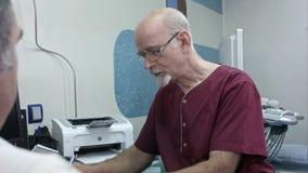Madure al doctor en su escritorio, haga algunas notas, escuchando un paciente mayor almacen de metraje de vídeo