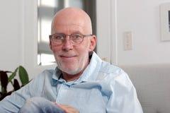 Madure al hombre calvo con las lentes que se sientan en el sofá Imagen de archivo libre de regalías