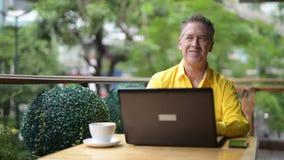 Madure al hombre que se sienta en cafetería mientras que usa el ordenador portátil y el teléfono móvil almacen de video