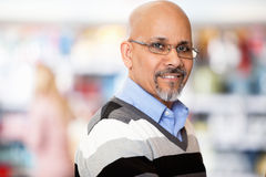 Madure al hombre que sonríe mientras que hace compras Imagen de archivo libre de regalías