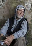Madure al hombre sin hogar que se sienta al aire libre con una lata Imágenes de archivo libres de regalías