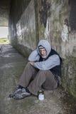 Madure al hombre sin hogar que se sienta al aire libre con una lata Imagen de archivo