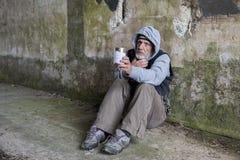Madure al hombre sin hogar que se sienta al aire libre sosteniendo hacia fuera una lata Foto de archivo