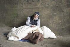 Madure al hombre sin hogar que se sienta en mantas viejas al aire libre Imagen de archivo
