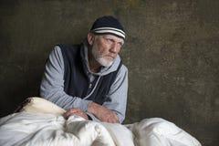 Madure al hombre sin hogar que se sienta en mantas viejas al aire libre Imagen de archivo libre de regalías