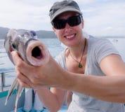 Madure al turista femenino que sonríe sosteniendo los pescados de Porae cogidos en fishi foto de archivo libre de regalías