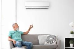 Madure el acondicionador de aire de funcionamiento del hombre mientras que se sienta en el sofá imágenes de archivo libres de regalías