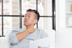 Madure el dolor asiático del hombro del hombre mientras que usa la tableta Imagen de archivo libre de regalías