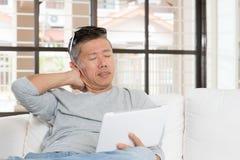 Madure el dolor de cuello asiático del hombre mientras que usa la tableta Imágenes de archivo libres de regalías