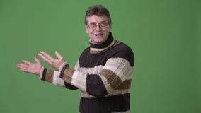 Madure el suéter del cuello alto del hombre que lleva hermoso contra fondo verde almacen de metraje de vídeo