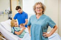 Madure la enfermera Standing With Couple y al bebé recién nacido Foto de archivo libre de regalías