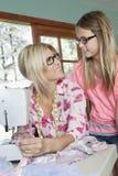 Madure a la madre que mira a la hija mientras que cose el paño Fotografía de archivo libre de regalías