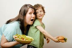 Madure a la mujer gorda que detiene la ensalada y al pequeño muchacho lindo Fotografía de archivo