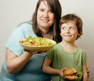 Madure a la mujer gorda que detiene la ensalada y al pequeño muchacho lindo Imagenes de archivo