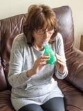 Madure a la señora atractiva que usa un dispositivo de respiración médico Imagen de archivo libre de regalías