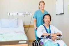 Madure la sentada paciente en la silla de ruedas mientras que enfermera Imagen de archivo