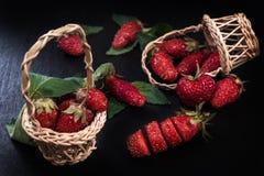 Madure las fresas rojas en una tabla negra y las fresas maduras frescas en una cesta de madera Imagen de archivo