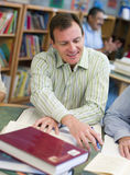 Madure a los estudiantes que estudian en biblioteca Foto de archivo