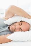 Madure los oídos soñolientos de la cubierta del hombre con la almohada en cama Foto de archivo