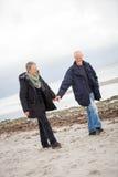 Madure los pares felices que caminan en la playa en otoño Imagen de archivo