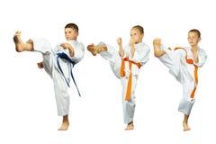 Mae-geri kick in perfoming three sportsmen in karategi collage. Mae-geri kick in perfoming three sportsmen in karategi Royalty Free Stock Photography