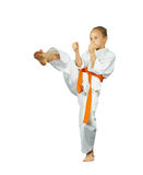 Mae-geri sportswoman beats with an orange belt. On the white background royalty free stock images