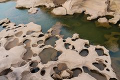 Mae Khong riverbed at Sam Phan Bok canyon in Thailand. Rock holes scattered all over the river bank in different shapes Royalty Free Stock Photography