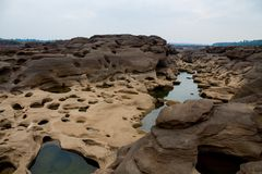 Mae Khong riverbed at Sam Phan Bok canyon in Thailand. Rock holes scattered all over the river bank in different shapes Stock Photo