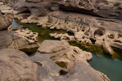 Mae Khong riverbed at Sam Phan Bok canyon in Thailand. Rock holes scattered all over the river bank in different shapes Royalty Free Stock Photo
