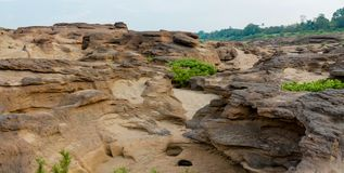 Mae Khong riverbed dry canyon. Mae Khong riverbed at Sam Phan Bok canyon in Thailand. rock holes scattered all over the river bank in different shapes Royalty Free Stock Photo