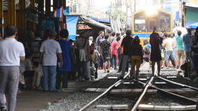 Mae Klong railway market. Samut Songkhram, Thailand-October 6, 2016: Whenever a train approaches, the awnings and shop fronts are moved back from the rails, to stock footage