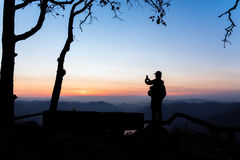 Mae Ping river view point. Silhouette woman taking a mountain sunrise photograph by mobile phone Stock Images