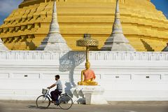 Man rides bicycle in front of the Wat Chumphon Khiri Buddhist stupa in Mae Sot, Tak province, Thailand. Mae Sot, Thailand - November 20, 2013: Unidentified man stock photos