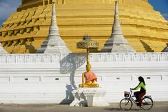 Woman rides bicycle in front of the Wat Chumphon Khiri Buddhist stupa in Mae Sot, Tak province, Thailand. Mae Sot, Thailand - November 20, 2013: Unidentified royalty free stock image