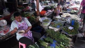 Maeklong Railway Market. MAEKLONG, THAILAND - MARCH 24: Vendor sells fresh local agricultural production on March 24, 2014 in famous Maeklong Railway Market also stock video footage