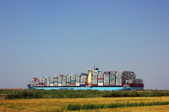 Maersk container ship. Passing Suez canal in Egypt beside land Stock Photo