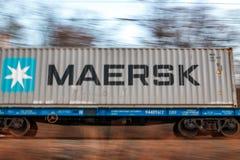 Maersk inskrift på en behållare som på flyttar en järnväg spårvagn mot bakgrunden av höstlandskapet av Ryssland i det avlägset fotografering för bildbyråer