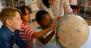 Maestra asiática joven que enseña a los niños sobre el globo en la tabla en la biblioteca escolar 4k almacen de video