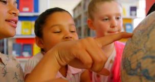 Maestra asiática que enseña a los niños sobre el globo en la tabla en la biblioteca escolar 4k almacen de video