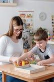 Maestro de jardín de infancia Supports Cute Boy en juego educativo del juego Fotografía de archivo libre de regalías
