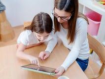 Maestro de jardín de infancia Supports Cute Girl en juego educativo del juego en la tableta digital Fotografía de archivo libre de regalías