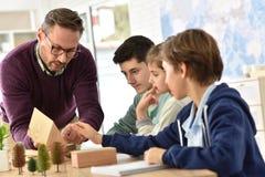 Maestro di scuola con gli allievi nella classe di scienza Fotografia Stock