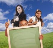 Maestro di scuola con i giovani studenti che tengono il bordo di gesso in bianco all'aperto Fotografie Stock Libere da Diritti