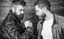 Mafia dealer. Real friendship of mature friends. Male friendship concept. Brutal bearded men wear leather jackets. Shaking hands. Real men and brotherhood stock photography