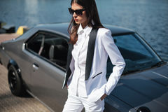 Mafia lady outside japanese car in the sea port. Fashion girl standing next to a retro sport car on the sun. Stylish woman in a white suit and sunglasses stock image