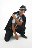 Mafia Man crouching staring at a subject Stock Photo