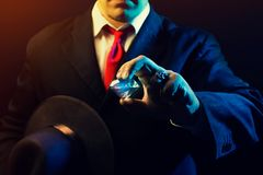Mafia man with a diamond. Mafia man holding hat & diamond on black background Stock Photos