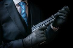 Mafia man or racketeer holds pistol with silincer in hands. Low key photo Stock Photo