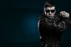Mafia man ready to hit with stick. Evil gangster man wearing leather coat and black sunglasses is ready to hit with his steel baton. Street wall background stock photography
